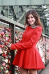 girl in red coat on bridge lock